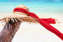 Sun hat with red scarf. Straw Hat on tropical island beach, sun hat with a red scarf at a seychelles beach Royalty Free Stock Photography