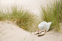 Sun hat and sandals on beach Stock Images