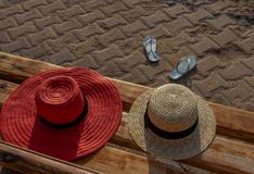 Sun hats on a bench and flip flops without owner royalty free stock photo