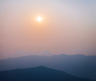 Sun and haze with silhouetted hills Royalty Free Stock Images