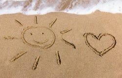 Sun and heart drawn on the sand Stock Photos