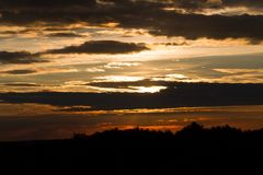 The sun hid behind the clouds. The sunset. The sun hid behind the clouds Stock Photos