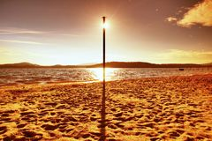 Sun hidden behind blue pole on sandy beach at sea. Forest hill on island in background Stock Photography