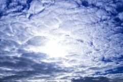 The sun is hidden behind numerous gray and blue clouds royalty free stock photo