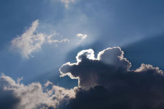 Sun hides behind clouds in sky Stock Image