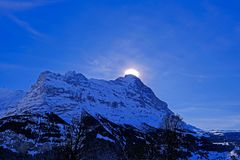 The sun hides behind the famous peak of the Eiger mountain above Grindelwald, with a lot of snow, Bern, Switzerland stock photos