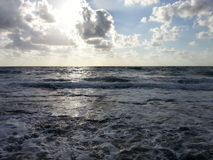 Sun hiding above sea Royalty Free Stock Photo