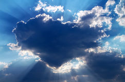 Sun hiding behind a cloud in the form of heart. On the day sky Stock Photos