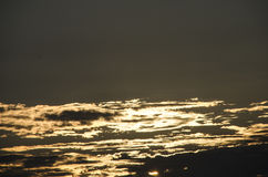 The sunset. The sun hiding behind the clouds royalty free stock photos