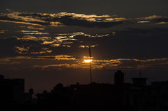 The sunset. The sun hiding behind the clouds stock image