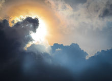 The sun hiding behind the clouds. Used as background Stock Images