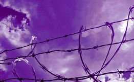 Sun Highlight on Razor Wire. Sunbeam shining through clouds to highlight area of barrier razor wire royalty free stock images