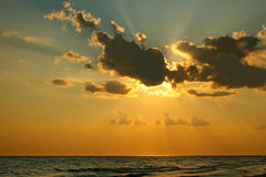 Sun hinter einer Wolke über Meer Stockfotos