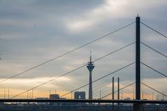 Sun hinter Wolken bewölktem DÃ ¼ sseldorf Fernsehturm überbrückt Stadttor-Landschaftsstadtbild Stockfoto
