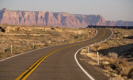 Curvy Two Lane Road Highway Biway Desert Southwest United States. The sun hits golden rock buttes behind a rise and bend in the road desert southwest USA royalty free stock image