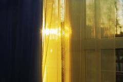 Sun hits the window through the curtain. The sun hits the window through the curtain Stock Images