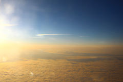 The sun illuminates the clouds in orange, the view from altitude Stock Photos