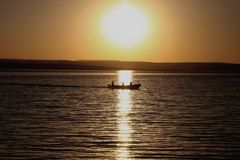 The sun illuminates the dawn of the day for the fishermen stock photo