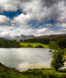 Loughrigg Tarn in Lake District. Sun illuminating Langdale Pikes with Loughrigg Tarn in foreground Royalty Free Stock Images