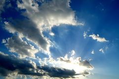 Sun irradia através das nuvens em um céu azul crepuscular Fotos de Stock