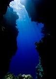 Sun irradia el filtro abajo a través del agua azul en una cueva del mar Fotos de archivo