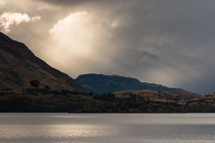 Sun irradia la fractura a través de las nubes sobre el lago Wanaka Fotos de archivo