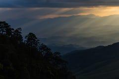 Sun irradia la fractura a través de las nubes sobre un paisaje de la montaña imagenes de archivo