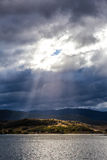 Sun irradia o brilho através das nuvens nos montes do lago Jindabyne, Foto de Stock
