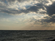 Sun irradia a projeção através das nuvens e no mar Imagens de Stock