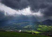 Sun irradia sobre o villiage nas montanhas imagens de stock