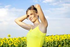 Sun-junges Mädchen auf dem Gebiet mit Sonnenblumen Stockfoto