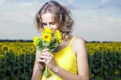 Sun-junges Mädchen auf dem Gebiet mit Sonnenblumen Stockbild