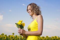 Sun-junges Mädchen auf dem Gebiet mit Sonnenblumen Stockfotografie