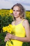 Sun-junges Mädchen auf dem Gebiet mit Sonnenblumen Lizenzfreie Stockbilder
