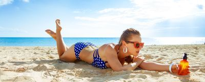 Active woman in beachwear on seacoast with sun block laying Royalty Free Stock Photo