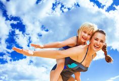 Cheerful young mother and daughter on beach having fun time Royalty Free Stock Photo