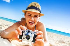 Happy healthy woman on beach taking photo with digital camera Royalty Free Stock Photos