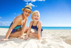 Smiling young mother and daughter in swimwear on seacoast. Sun kissed beauty. Portrait of smiling young mother and daughter in swimwear on the seacoast Royalty Free Stock Images
