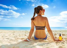 Healthy woman in beachwear on seashore looking into distance Stock Photography