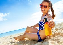 Smiling fit woman in beachwear on the seashore with sun cream Royalty Free Stock Image