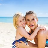 Smiling healthy mother and daughter on seashore embracing. Sun kissed beauty. smiling healthy mother and daughter in beachwear on the seashore embracing Royalty Free Stock Photography