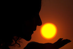 Sun kissing. Young female is kissing the Sun during sunrise royalty free stock photo