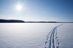 Sun, la nieve y el esquí siguen cruzar un lago congelado Imagenes de archivo