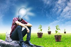 The sun in lamp man and small plant on landscapes background Royalty Free Stock Images