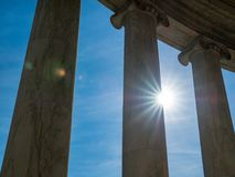 Sun, with some lens flair, shining through marble building columns. Sun, with lens flair, shining through marble building columns royalty free stock images