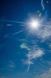 Sun with lens flare, on blue sky background. Stock Images