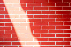 Sun-Lichtglanz an der Wand des roten Backsteins, Beschaffenheitshintergrund Stockfotografie