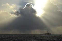 Sun light beams over Oil platform royalty free stock photography