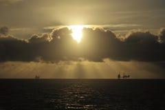Sun light beams over Oil platform stock image