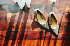 The sun light through curtain, the glittering shoes with shadow on the wooden floor. High heels, pumps stock photos